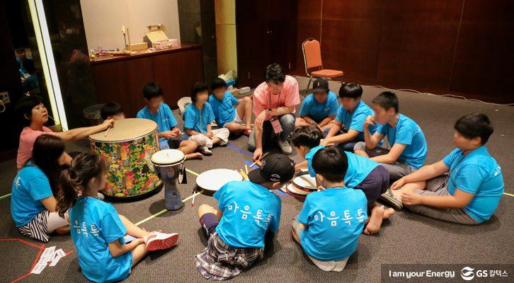 아이들이 바닥에 둘러앉아 치료사 선생님의 북소리를 들으며 노래로 속마음을 이야기하고 있다.