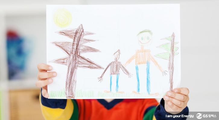 아이가 자신의 그림을 들고 서 있다.