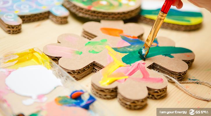 아이가 골판지로 만든 조형물에 물감을 칠하고 있다
